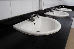Liquid soap box and white sinks in public toilet room. Royalty Free Stock Images