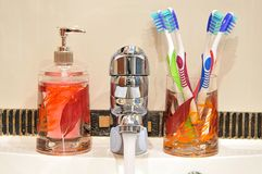 Liquid Soap, Faucet and Four Toothbrushes Stock Photo