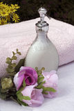 Liquid soap and flowers. Liquid soap a pink towel and silk flowers royalty free stock image