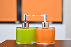 Liquid soap dispensers. Orange and green liquid soap dispensers stock image