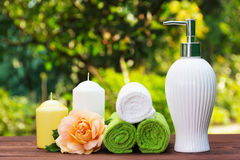 Liquid soap, a stack of towels, candles and a fragrant rose. Spa set for body care. Spa concept. Liquid soap, a stack of towels, candles and a fragrant rose stock photos