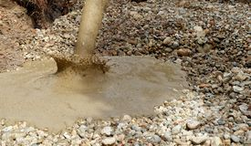 Liquid soil is poured from the concrete mixer onto the floor of the excavation pit covered with coarse gravel and stones. stock photos