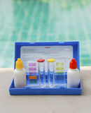 Liquid swimming pool water testing test kit. Over swimming pool background, summer outdoor day light stock image