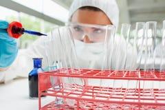 Liquide de baisse protégé de scientifique dans un tube à essai images libres de droits