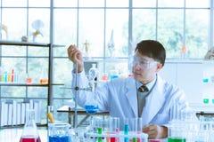 Liquide de chute de scientifique dans le tube ? essai bleu photo libre de droits