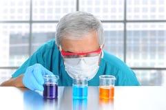 Liquide de examen de scientifique dans des bechers Photographie stock libre de droits