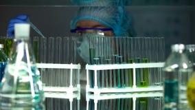 Liquide de ?gouttement de technicien de laboratoire dans le tube, produisant des lotions de dermatologie, examinant photographie stock
