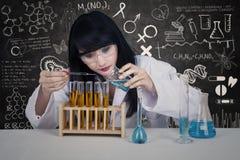 Liquide de versement de beau scientifique dans la classe image libre de droits