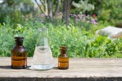 Liquide en articles chimiques sur un fond des usines, des engrais ou des pesticides dans le jardin images stock