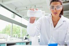 Liquide pleuvant à torrents d'étudiant féminin de la science photo libre de droits