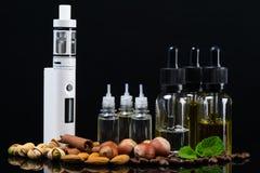 Liquide pour une cigarette électronique dans les bulles entourées par les écrous, la cannelle et la menthe fraîche Images libres de droits