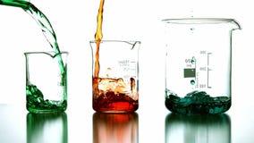 Liquides chimiques versant dans le becher banque de vidéos