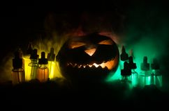 Liquides colorés de vape avec le potiron de Halloween sur le fond foncé Concept de Vape Images stock