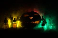 Liquides colorés de vape avec le potiron de Halloween sur le fond foncé Concept de Vape Photographie stock