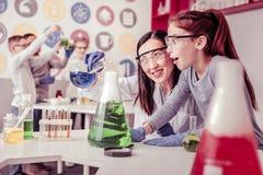 Liquides de mélange de lancement de professeur aux cheveux longs dans la grande ampoule photographie stock