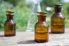 Liquido in articoli chimici su un fondo delle piante, dei fertilizzanti o degli antiparassitari nel giardino Immagine Stock