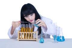 Liquido d'esame dello scienziato attraente su bianco Immagine Stock