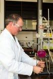 Liquido del riscaldamento del chimico in boccetta di vetro Immagini Stock