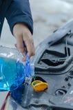 Liquido di versamento dell'antigelo per lavare lo schermo dell'automobile fotografia stock