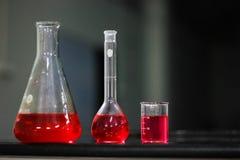 Liquido rosso in boccetta basata rotonda e boccetta conica di vetro e del becher su una tavola nera del granito nel fondo scuro fotografia stock