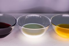 Liquids of different colors in glass plates. stock photo