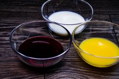 Liquids of different colors in glass plates. Liquids of different colors in glass plates on a wooden table royalty free stock photography