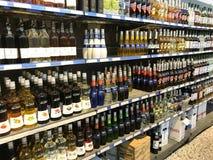 Liquor bottles in rows of aisles and shelves in supermarket. Copenhagen, Denmark - April 19, 2019 royalty free stock photos