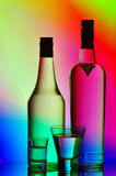Liquor bottles and shot glasses. Collection of spirits - vodka and liquor bottles with shot glasses against vibrant gradient background Royalty Free Stock Photos