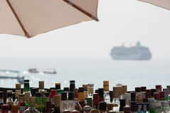 Liquor Bottles in a Tropical Beach Bar with Cruise Boat Stock Photos