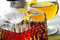 Liquor. Closeup of a vintage glass liquor bottle and some cognac glasses with liquor Stock Photography