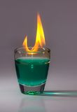 Liquor on fire. A burning glass full of liquor Stock Photos