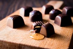 Liquor is flowing from the chocolate on wooden surface. Royalty Free Stock Images