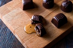 Liquor is flowing from the chocolate on wooden surface. Royalty Free Stock Photos