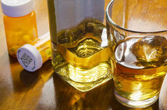 Liquor with pills. Closeup of liquor bottle with glass and medication bottles Royalty Free Stock Image