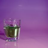 Liquor Shot or shotter. A shot glass filled with liquor and ready to shoot with a contrasty background and square crop Stock Images