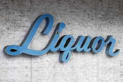 Liquor Sign. A weathered and cracked sixties Liquor store sign on a wall Stock Photography