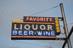 Liquor sign with blue sky in the background. A multi colored neon sign reading Liquor Beer Wine Royalty Free Stock Image