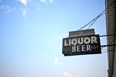 Liquor store sign. Neon sign above an abandoned liquor and beer store.  Blue sky background Royalty Free Stock Photography