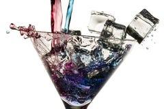Liquore rosso e blu versato in un vetro Fotografia Stock