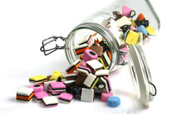 Liquorice all sorts. Glass bottle with colorful liquorice all sorts on a white background Royalty Free Stock Photography