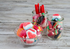 Liquorice,candies and sweets in glass jars on wooden table Stock Images