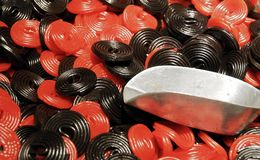Liquorice wheels at a sweets shop with a food pliers stock images