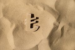 Lira Symbol Under the Sand. Turkish Lira Symbol or Sign Covered with Sand in the Sun after Crisis stock photo
