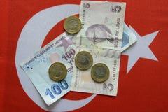 Lira turca de la divisa nacional en bandera turca fotografía de archivo