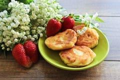Lirio de los valles del ramo de la primavera, pasteles de queso con las fresas Desayuno de los pasteles de queso del requesón Pri imágenes de archivo libres de regalías