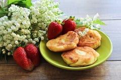 Lirio de los valles del ramo de la primavera, pasteles de queso con las fresas Desayuno de los pasteles de queso del requesón Pri foto de archivo