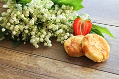 Lirio de los valles del ramo de la primavera, pasteles de queso con las fresas Desayuno de los pasteles de queso del requesón Pri fotografía de archivo