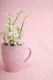 Lirio de los valles en taza rosada Imagen de archivo libre de regalías