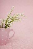 Lirio de los valles en taza rosada Imágenes de archivo libres de regalías