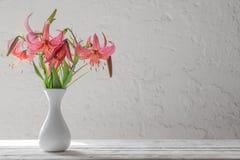 Lirio en florero en la pared del blanco del fondo imágenes de archivo libres de regalías